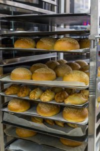 fresh hot buns in handcart from oven
